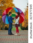 boy and girl among the leaves... | Shutterstock . vector #327377345