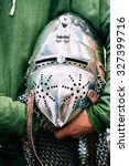 Small photo of Iron Helmet Of The Medieval Knight. Helmet Of A Medieval Suit Of Armour In Hands
