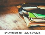 Small photo of records stack with record on top over wooden table. vintage filtered