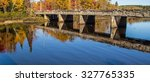 Autumn Road Trip. Concrete bridge reflection framed by fall foliage in panoramic orientation. Michigamme, Michigan.