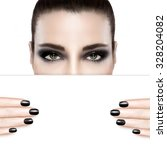 Dark smoky beauty and nail art concept with a woman wearing creative dark eye makeup holding a blank white card template covering her mouth with matching dark manicured nails.  - stock photo