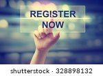 Small photo of Hand pressing Register Now on blurred cityscape background