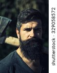 Small photo of One handsome strong stylish male logger of young man with long lush black beard and moustache in shirt holding wooden axe standing in forest outdoor on natural background, vertical picture
