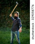 Small photo of One handsome strong stylish male logger of young man with long lush black beard and moustache in shirt holding wooden axe standing near wall with climber plant outdoor, vertical picture
