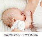 young mother breastfeeds her... | Shutterstock . vector #329115086