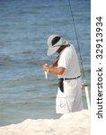 Fisherman On Seashore Removing...