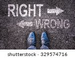 Small photo of Feet and words right and wrong painted on an asphalt road