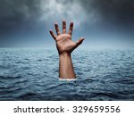 Small photo of Drowning hand in stormy sea asking for help