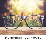 Small photo of hipster glasses on a park bench or table with a forest in the background toned with a retro vintage instagram filter app or action effect