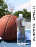 Basketball and bottled water on basketball court - stock photo