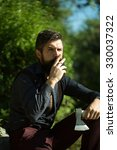 Small photo of One strong stylish male logger of young man with long lush black beard and moustache in shirt holding wooden axe sitting in forest smoking cigarette outdoor on natural background, vertical picture