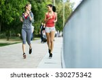 two sporty women jogging in... | Shutterstock . vector #330275342