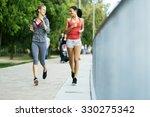 two sporty women jogging in... | Shutterstock . vector #330275342