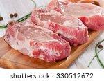 pork steaks on a wooden board.... | Shutterstock . vector #330512672