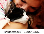 Stock photo young happy smiling red haired girl dressed in hippie bohemian style hugging cat outdoors 330543332