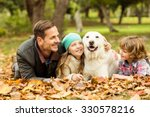 Smiling Young Family With Dog...