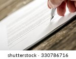 Small photo of Man signing business document, application, subscription form or insurance papers with silver pen on wooden desk.