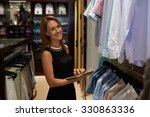 Small photo of Half length portrait of happy female entrepreneur using digital tablet for job in her modern store with men's clothes, smiling woman owner or consultant holding touch pad while standing in brandy shop