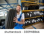 Smiling Auto Mechanic Carrying...