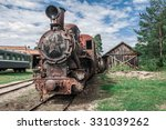 Old rusty steam train locomotive sitting on old rail track in the middle of nowhere - stock photo