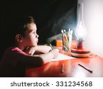 Small photo of boy writes letter to Santa Claus. boy writes in the lamplight