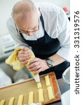 baker prepares a cake and... | Shutterstock . vector #331319576