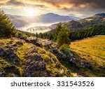 view from a rocky cliff to full of fog valley with conifer forest in high mountains of Apuseni Natural Park in Romania in evening light - stock photo