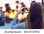 Woman hands showing heart science on sunset, young woman travel alone, love concept, posing opposite sunset, fashion accessorizes, sunset in Miami, view on palms.