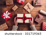 Man holding Christmas presents laid on a wooden table background - stock photo