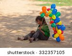 Small photo of JAIPUR,INDIA - March 30, 2013 : Unidentified poor child tries to sell balloons and eats food that she can find in the streets of the city.