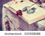 Old book  and a dried red rose  ...