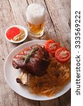 Small photo of eisbein: baked pork shank and braised cabbage closeup on a plate and beer on the table. vertical
