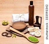 Small photo of Spa and pampering products and accessories: sea salt, pumice, loofah, wisp of bast, bamboo plate with water, crock, shower gel, bath towel on wooden surface