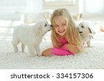 Stock photo little girl lying on the mat with labrador smiling at camera at home in the living room 334157306