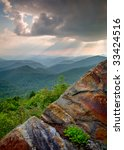 Sun Beams and Rays over Blue Ridge Mountains Rock landscape with flowers - stock photo