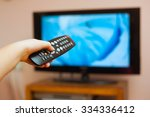 kid holding tv remote controller | Shutterstock . vector #334336412