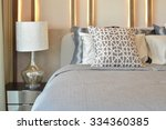 Stock photo stylish bedroom interior design with brown pillows on bed and decorative table lamp 334360385