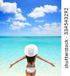 Small photo of Beach woman standing with arms outstretched against turquoise sea and blue sky. Rear view of female wearing white sunhat and bikini. Carefree tourist is enjoying vacation at beach.