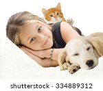 Stock photo beautiful girl and kitten and puppy lying on the sofa 334889312