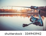 hand with spinning and reel on... | Shutterstock . vector #334943942