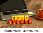 Stock photo open source written on a wooden cube in front of a laptop 334982726