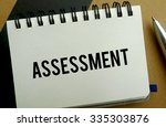 Assessment memo written on a notebook with pen - stock photo