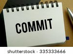 Commit memo written on a notebook with pen - stock photo