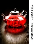 glass teapot with red tea with...