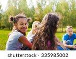 happy international teens sit... | Shutterstock . vector #335985002