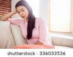 upset asian woman on couch at... | Shutterstock . vector #336033536