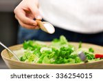 young woman making salad in the ... | Shutterstock . vector #336254015