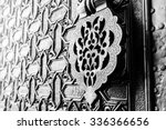 Small photo of Detail of an islamic door knocker and ornaments outside one of the main entrance gates to the Cathedral of Seville, Spain. Shallow DOF, toned.