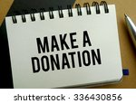 Make a donation memo written on a notebook with pen - stock photo