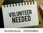 Volunteer needed memo written on a notebook with pen - stock photo